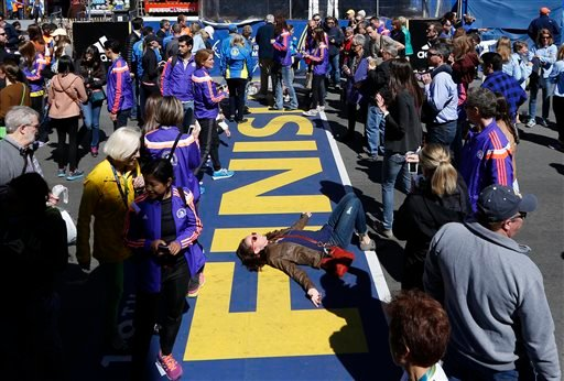 A woman poses at the Boston Marathon finish line, a day ahead of the 119th running of the race, Sunday, April 19, 2015, in Boston, Mass. (AP Photo/Robert F. Bukaty)