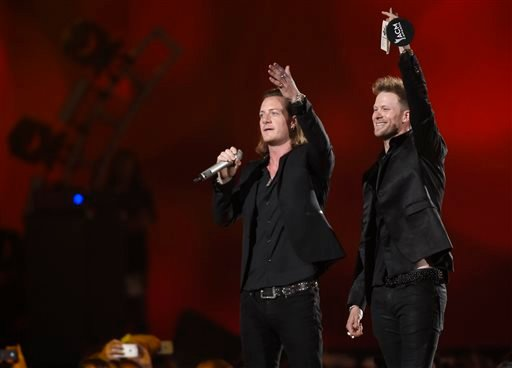 Tyler Hubbard, left, and Brian Kelley, of Florida Georgia Line, accept the award for vocal duo of the year at the 50th annual Academy of Country Music Awards at AT&T Stadium on Sunday, April 19, 2015, in Arlington, Texas. (Photo by Chris Pizzello/Invision