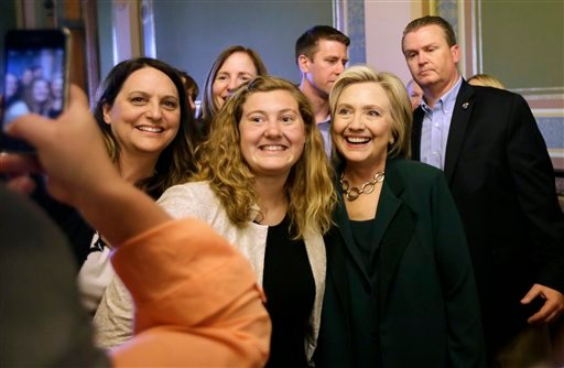 Democratic presidential candidate Hillary Rodham Clinton poses for a photo with Simpson College student MacKenzie Bills, center, after meeting with Iowa Democratic Party lawmakers at the Statehouse, Wednesday, April 15, 2015, in Des Moines, Iowa. (AP Phot