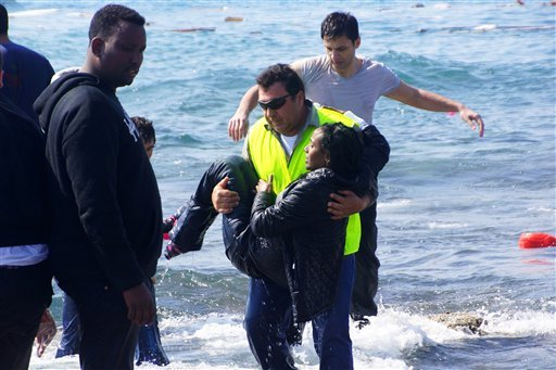 A man rescues a migrant from the Aegean sea, in the eastern island of Rhodes, Monday, April 20, 2015. Greek authorities said that at least three people have died, including a child, after a wooden boat carrying tens of migrants ran aground off the island