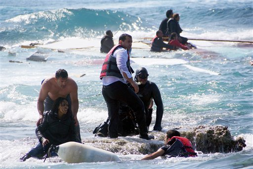 A man rescues an migrant from the Aegean sea, in the eastern island of Rhodes, Monday, April 20, 2015. Greek authorities said that at least three people have died, including a child, after a wooden boat carrying tens of migrants ran aground off the island