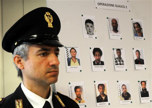 An Italian Police officer stands next to mug shots of alleged migrant traffickers shown during a press conference, in Palermo, Sicily, Italy, Monday, April 20, 2015. Police in southern Italy has broken up a major human smuggling ring responsible for the w