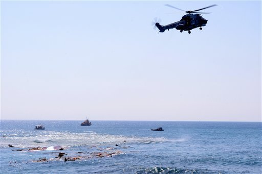 A helicopter flies over the wreckage of a boat which was carrying dozens of migrants in the eastern Aegean island of Rhodes, Greece on Monday, April 20, 2015 .Greek authorities said that at least three people have died, including a child, after a wooden b