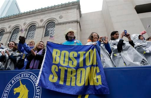 "Carlos Arredondo, a 2013 Boston Marathon first-responder, holds a ""Boston Strong"" banner beside his wife Melida, right, in the grandstand near the Boston Marathon finish line Monday, April 20, 2015 in Boston."