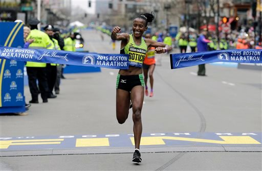 Caroline Rotich, of Kenya, breaks the tape to win the women's division of the Boston Marathon, Monday, April 20, 2015 in Boston.