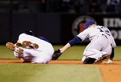 San Diego Padres shortstop Clint Barmes (12) applies the tag without the ball to Colorado Rockies' Nick Hundley during the fourth inning of a baseball game Monday, April 20, 2015, in Denver. (AP Photo/Jack Dempsey)