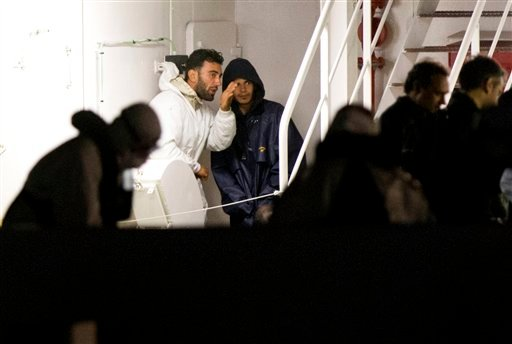 Mohammed Ali Malek, left, and Mahmud Bikhit, two of the survivors of the boat that overturned off the coasts of Libya Saturday, wait to disembark from Italian Coast Guard ship Bruno Gregoretti, at Catania Harbor, Italy, Monday, April 20, 2015. Mohammed Al