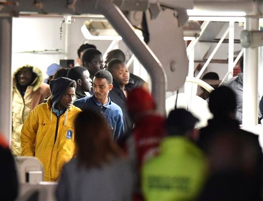 Survivors of the boat that overturned off the coasts of Libya Saturday, wait to disembark from Italian Coast Guard ship Bruno Gregoretti, at Catania Harbor, Italy, Monday, April 20, 2015. A smuggler's boat crammed with hundreds of people overturned off Li
