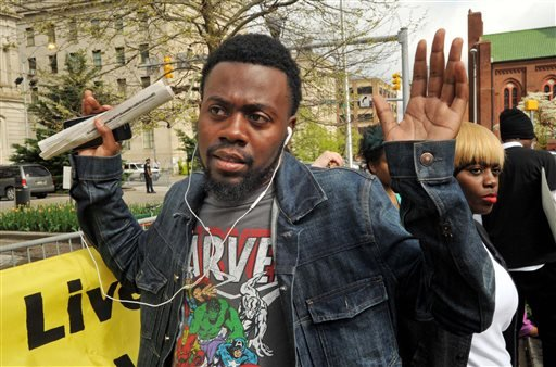 "William Stewart, a friend of Freddie Gray, protests outside City Hall in Baltimore, Monday, April 20, 2015. Baltimore's top police officials, mayor and prosecutor sought to calm a ""community on edge"" Monday while investigating how Gray suffered a fatal sp"