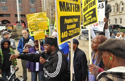 "The Rev. Cortly ""C.D."" Witherspoon, front left, president of the Baltimore City chapter of the Southern Christian Leadership Conference, speaks at a protest outside City Hall about Freddie Gray in Baltimore, Monday, April 20, 2015. Baltimore's top police"