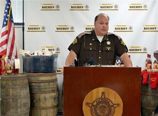 Franklin County Sheriff Pat Melton, standing in front of some of the recovered evidence, responds to a question during a press conference in Frankfort, Ky., April 21, 2015. (AP Photo/Timothy D. Easley)
