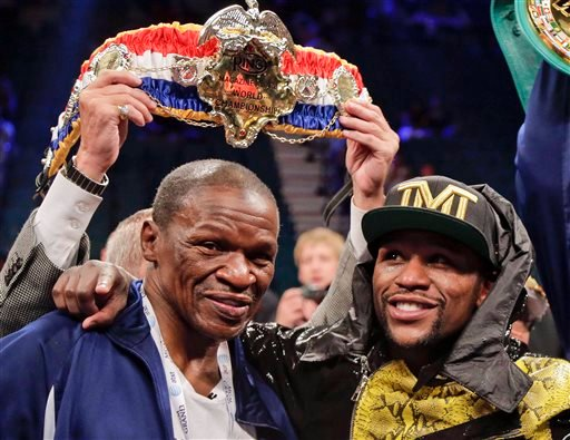 In this May 4, 2013, file photo, Floyd Mayweather Jr., right, poses for photos with his father, Floyd Mayeather Sr.