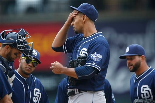 San Diego Padres starting pitcher Tyson Ross, center, reacts as he confers with, from left, catcher Wil Nieves, shortstop Alexi Amarista and first baseman Yonder Alonso.