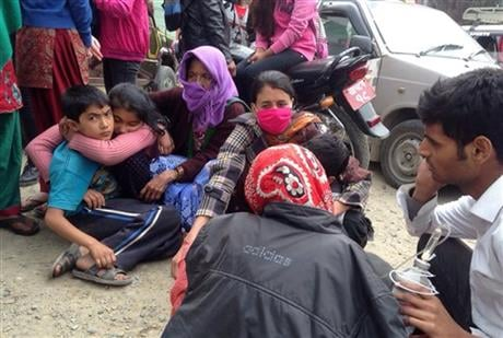 © Nepalese people huddle together outside the Medicare Hospital in Kathmandu, Nepal, Saturday, April 25, 2015. A strong magnitude-7.9 earthquake shook Nepal's capital and the densely populated Kathmandu Valley before noon Saturday, causing extensive damag