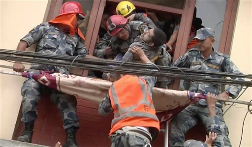 In this image made from video, rescue workers pull a survivor from an earthquake damaged building in Kathmandu, Nepal, Sunday, April 26, 2015. (APTN via AP)