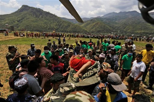 Nepalese soldiers carry a wounded woman to a waiting Indian air force helicopter as they evacuate victims of Saturday's earthquake from Trishuli Bazar to Kathmandu airport in Nepal, Monday, April 27, 2015. The death toll from Nepal's earthquake is expecte