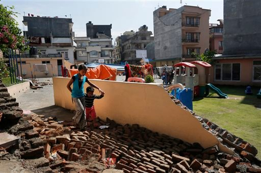 A young girl walks with a boy over a collapsed school playground in Kathmandu, Nepal, Monday, April 27, 2015. A strong magnitude 7.8 earthquake shook Nepal's capital and the densely populated Kathmandu Valley on Saturday, causing extensive damage with top