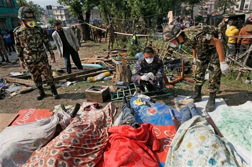 Rescue teams' members identify bodies dug out of the collapsed Sitapyla church in Kathmandu, Nepal, Monday, April 27, 2015. A strong magnitude 7.8 earthquake shook Nepal's capital and the densely populated Kathmandu Valley on Saturday, causing extensive d