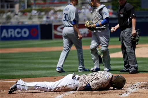 San Diego Padres' Yangervis Solarte, below, stays down after being tagged out at home off a hit for a double by the Padres' Matt Kemp during the first inning of a baseball game against the Los Angeles Dodgers Sunday, April 26, 2015, in San Diego. (AP Phot