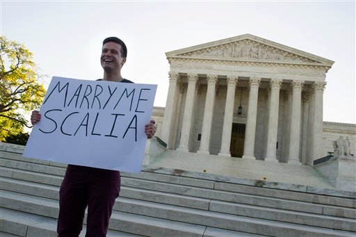 Ryan Aquilina, 24, of Washington holds a sign in front of the Supreme Court in Washington, Tuesday, April 28, 2015. The Supreme Court is set to hear historic arguments in cases that could make same-sex marriage the law of the land. The justices are meetin