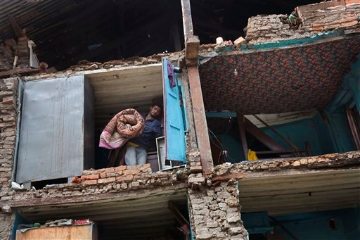A resident carries his belongings retrieved from the ruins of his home after Saturday's earthquake in Bhaktapur, Nepal, Tuesday, April 28, 2015. Many people have camped outdoors in the chilly night cold since Saturday's massive earthquake that shook Nepal