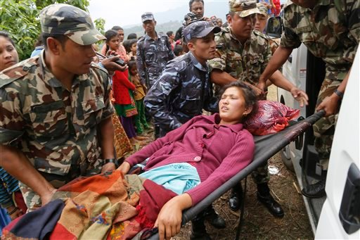Sita Karka, suffering two broken legs from Saturday's massive earthquake, is assisted into an ambulance by Nepalese soldiers and police after arriving by helicopter from the heavily-damaged Ranachour village at a landing zone in the town of Gorkha, Nepal,