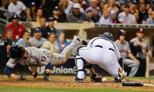 Houston Astros' Jed Lowrie is safe at home as he sails over San Diego Padres catcher Derek Norris in the eighth inning of a baseball game Monday, April 27, 2015, in San Diego. Lowrie scored on a base hit by Colby Rasmus. (AP Photo/Lenny Ignelzi)