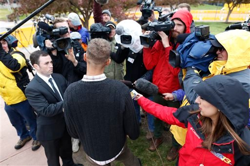 Surrounded by television photographers and reporters, Marcus Weaver, front, a victim of the shooting massacre at an Aurora, Colo., theatre, talks at the conclusion of the opening day of the trial for theatre shooting suspect James Holmes Monday, April 27,