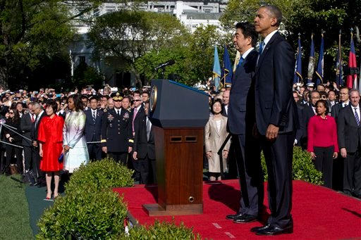 President Barack Obama hosts a state arrival ceremony for Japanese Prime Minister Shinzo Abe, Tuesday, April 28, 2015, on the South Lawn of the White House in Washington. Abe's wife Akie Abe, left in red, and first lady Michelle Obama are at left. (AP Pho