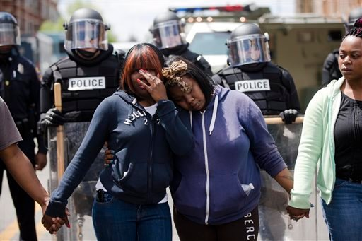 Jerrie Mckenny, center left, and her sister, Tia Sexton embrace as people sing the hymn Amazing Grace April 28, 2015, in Baltimore, in the aftermath of rioting following Monday's funeral for Freddie Gray, who died in police custody (AP Photo/Matt Rourke)
