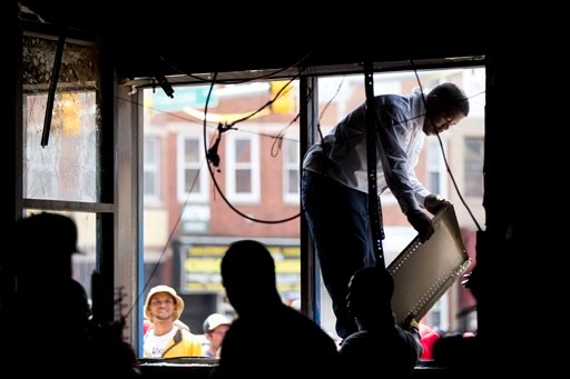 Volunteers clean a CVS pharmacy April 28, 2015, in Baltimore, in the aftermath of rioting following Monday's funeral for Freddie Gray, who died in police custody. (AP Photo/Matt Rourke)