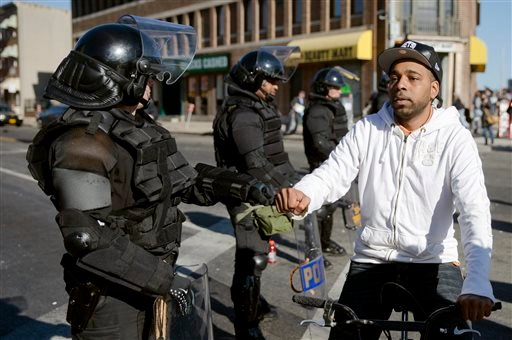 A man on a bicycle greets Maryland State Troopers April 28, 2015, in the aftermath of rioting following Monday's funeral for Freddie Gray, who died in police custody. (AP Photo/Matt Rourke)