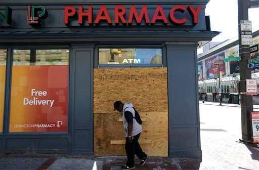 A store entrance is boarded up as a pedestrian walks through downtown, Wednesday, April 29, 2015, in Baltimore. (AP Photo/David Goldman)