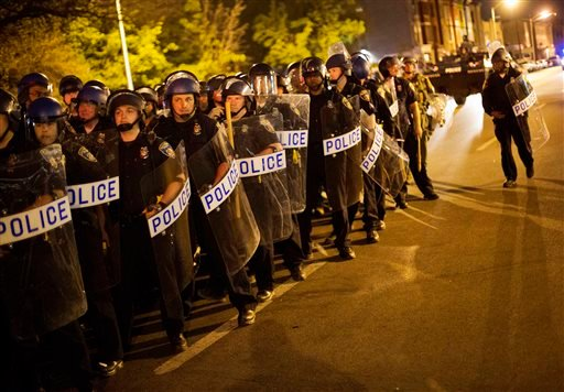 Police in riot gear line up near the scene of Monday's riots ahead of a 10 p.m. curfew April 29, 2015, in Baltimore. The curfew was imposed after unrest in Baltimore over the death of Freddie Gray while in police custody. (AP Photo/David Goldman)