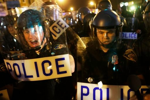 Police in riot gear push back on media and a crowd gathering in the street after a 10 p.m. curfew went into effect Thursday, April 30, 2015, in Baltimore. The curfew was imposed after unrest in the city over the death of Freddie Gray while in police custo