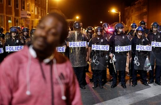A protester walks past a line of police as they enforce curfew for the third night, Thursday, April 30, 2015, in Baltimore. (AP Photo/Patrick Semansky)