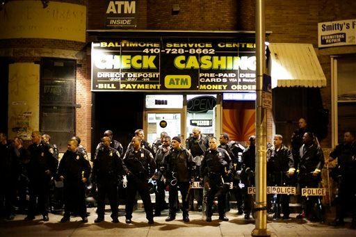 Police wait on a sidewalk as a crowd gathers Thursday, April 30, 2015, in Baltimore. The curfew was imposed after unrest in the city over the death of Freddie Gray while in police custody. (AP Photo/David Goldman)