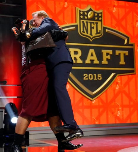 Washington defensive lineman Danny Shelton picks up NFL commissioner Roger Goodell as he celebrates after being selected by the Cleveland Browns as the 12th pick in the first round of the 2015 NFL Draft, Thursday, April 30, 2015, in Chicago. (AP Photo/Cha