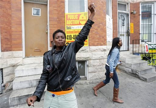 Renay Battle, left, and Charvae Day, right, react to the news from State's Attorney Marilyn Mosby that there are probable causes to charge those involved in the police-custody death of Freddie Gray Friday, May 1, 2015, as they walk through the area of Mon