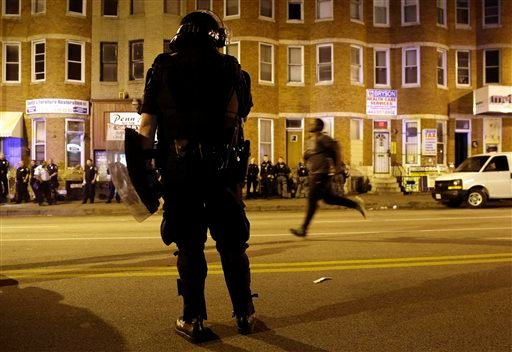A police officer watches as a man runs down North Avenue as a curfew approaches, Thursday, April 30, 2015, in Baltimore. (AP Photo/Patrick Semansky)