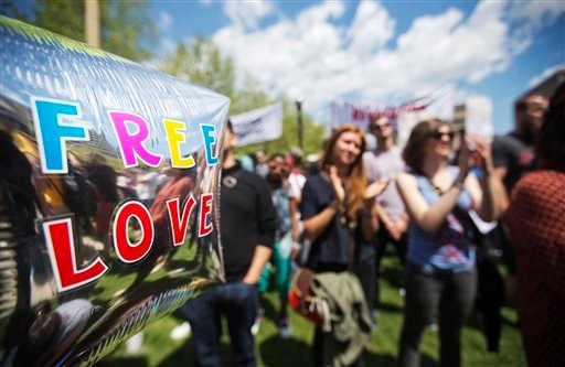 "A balloon with a message reading ""Free Love"" floats amongst the crowd during a demonstration at City Hall in Baltimore Saturday, May 2, 2015, the day after charges were announced against the police officers involved in Freddie Gray's death. (AP Photo/Davi"