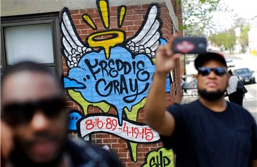 J.R. White, right, takes a selfie in front of a mural that was painted at the site of Freddie Gray's arrest, Saturday, May 2, 2015, in Baltimore, as protesters prepare to march to City Hall. Six police officers were charged Friday with felonies ranging fr