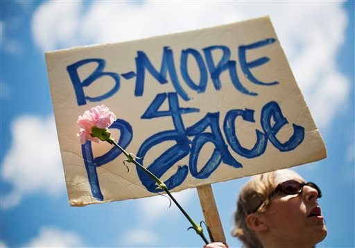 """Kate Manger, of Baltimore, holds a sign with a flower while attending a demonstration at City Hall the day after charges were announced against the police officers involved in Freddie Gray's death, Saturday, May 2, 2015 in Baltimore. """"The city is in need"""