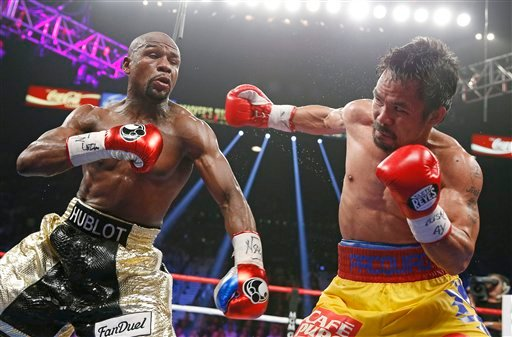 Manny Pacquiao, from the Philippines, right, throws a right against Floyd Mayweather Jr., during their welterweight title fight on Saturday, May 2, 2015 in Las Vegas.
