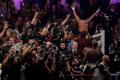 Floyd Mayweather Jr., bottom right, watches as Manny Pacquiao, from the Philippines, waves to the crowd at upper right after their welterweight title fight on Saturday, May 2, 2015 in Las Vegas.