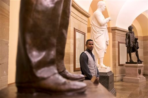 In this photo taken on Friday, May 1, 2015, Abraham Tesfahun, 21, who works in food service at the Senate and makes $10.70 an hour, poses for a portrait at the Capitol in Washington. Income inequality is more than a political sound bite to workers in the