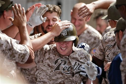 San Diego Padres' Jedd Gyorko, center, is greeted by teammates in the dugout after hitting a two-run home run against the Colorado Rockies during the sixth inning of a baseball game Sunday, May 3, 2015, in San Diego. (AP Photo/Gregory Bull)