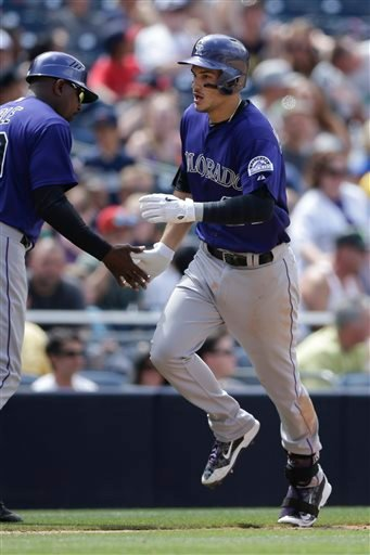 Colorado Rockies' Nolan Arenado is greeted by third base coach Stu Cole after hitting a two-run home run against the San Diego Padres during the fourth inning of a baseball game Sunday, May 3, 2015, in San Diego. (AP Photo/Gregory Bull)