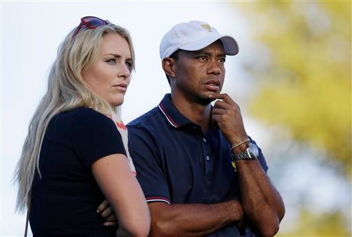 This Oct. 3, 2013 file photo shows Tiger Woods watching with his girlfriend Lindsey Vonn at the Presidents Cup golf tournament at Muirfield Village Golf Club in Dublin, Ohio.