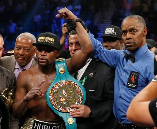 Floyd Mayweather Jr., left, holds up the title belt next to referee Kenny Bayless after his win against Manny Pacquiao, from the Philippines, in their welterweight title fight on Saturday, May 2, 2015 in Las Vegas.